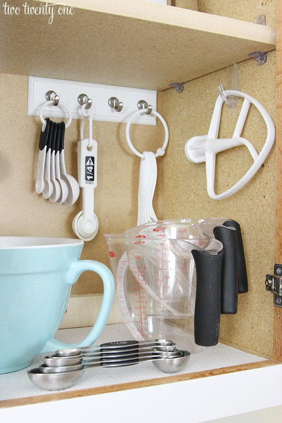 Organize kitchen cabinet with hooks for measuring spoons and other baking utensils. (Image and Tip Credit: Two Twenty One)