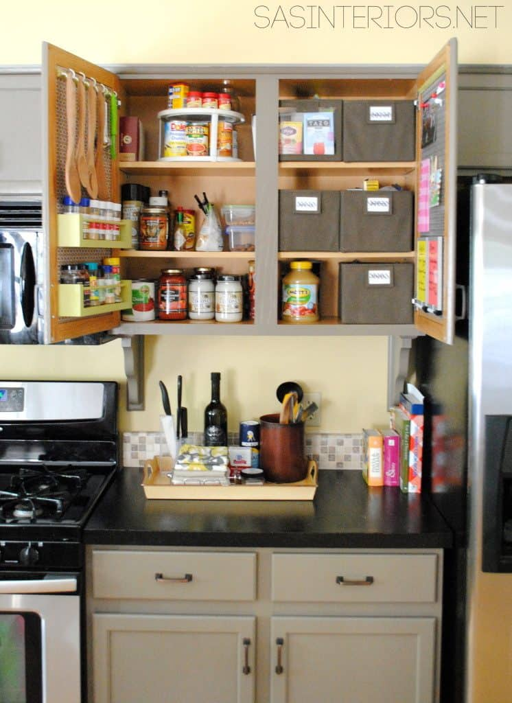 Kitchen cabinet organized with baskets, lazy susan and shelves and hooks on the cabinet doors.