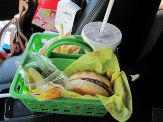 A craft caddy used as a snack tray in a car.