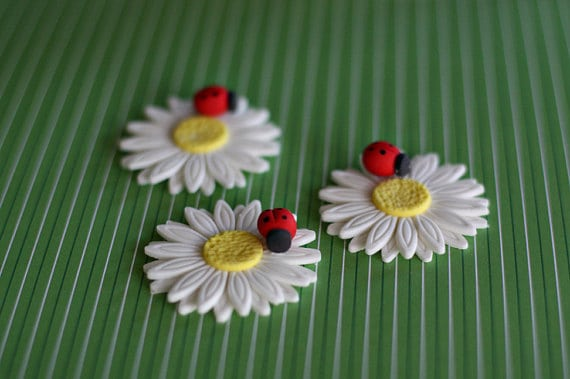 Fondant daisy and a lady bug cupcake topper. A cute snuggle bug baby shower idea! (image credit: Parkers Flour Patch)