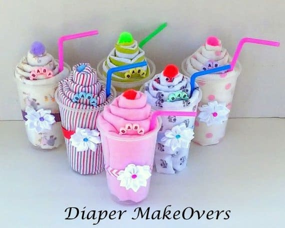 Perfect decoration for an ice cream baby shower! These receiving blanket milkshakes make also an awesome baby shower gift. (Image of receiving blanket rolled up inside a clear cup garnished with a pom pom and a straw.Image: Diaper Makeover)