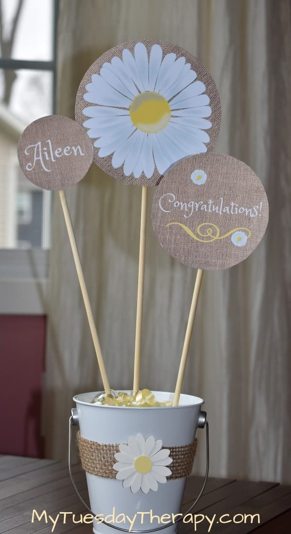 Daisy Centerpiece DIY. Burlap wrapped around a white bucket. A cute white daisy attached to it.