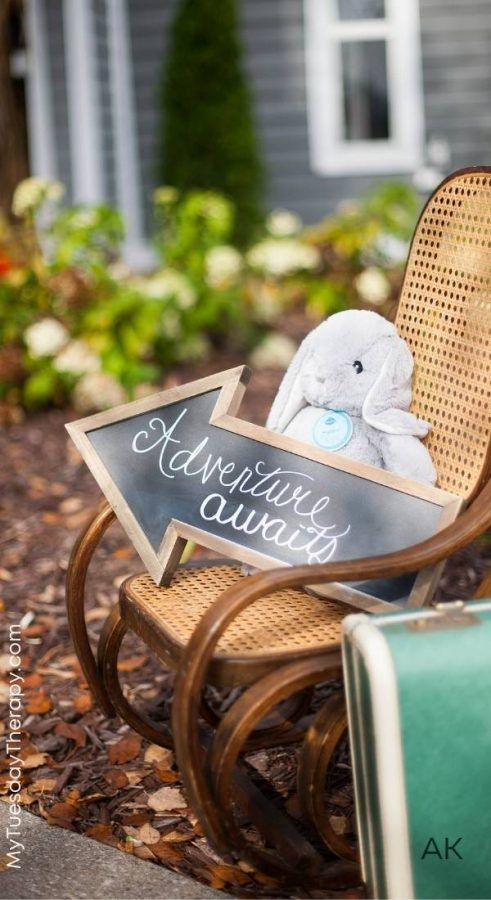 Adventure Awaits Baby Shower Decorations. A vintage kids' rocking chair, a bunny and an adventure awaits chalkboard arrow sign. A vintage suitcase next to the rocking chair.