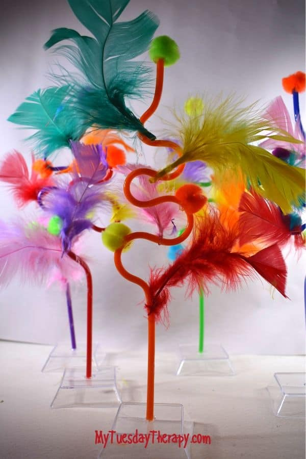 Easy DIY Dr. Seuss party decoration. Seussified straws with pom poms and feathers.