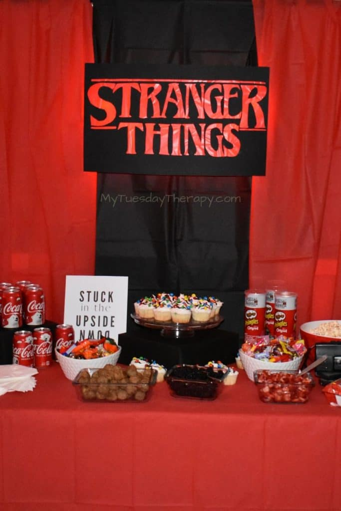 Stranger Things Party DIY Sign with Lights used as a cool backdrop for the food table