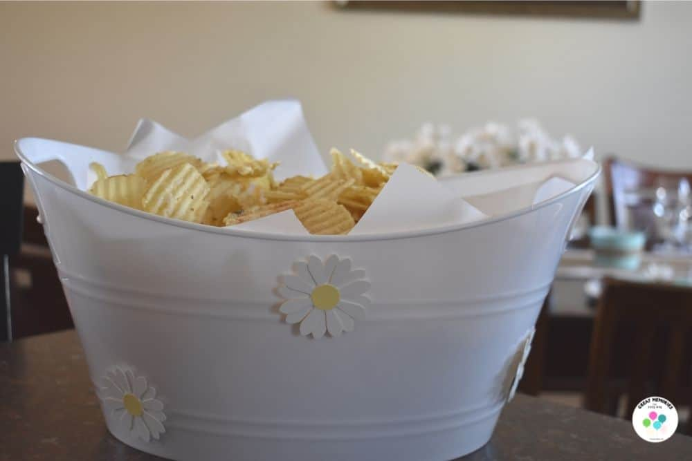 Daisy themed bucket for serving chips at daisy graduation party.