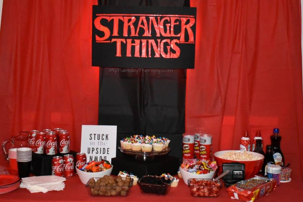 Stranger Things Party Food Table Ideas. Stranger Things DIY sign, red and black backdrop.