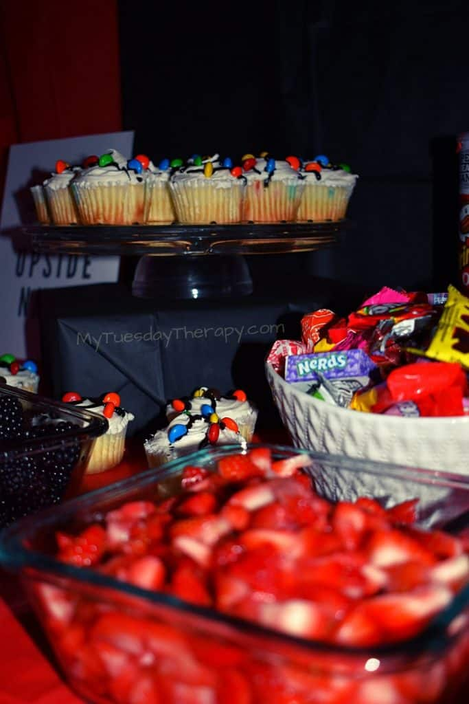Stranger Things Party Food: Christmas lights cupcakes, strawberries, a candy bowl.