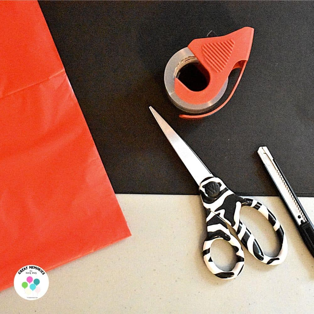 What you need for making a stranger things diy sign: black poster board paper, red plastic tablecloth, tape, scissors, craft knife....
